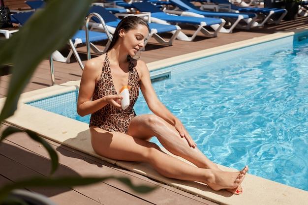 スイミングプールのそばに座って、休日を楽しんで、片手でボトルを握り、日光浴用のクリームを彼女の肌に注意深く塗布する細身の磁気美女、スキンケア。夏の時間の概念。
