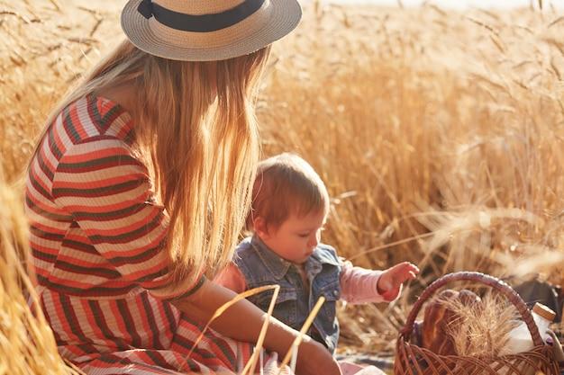 麦畑で小さな娘と一緒に座って、一緒に小さなピクニックをしている若い金髪の母親の屋外の写真。