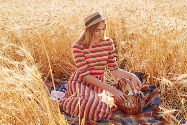 Портрет привлекательной нежной молодой леди, проводить время в одиночестве на пшеничном поле, сидя на одеяле, касаясь корзины руками, собираясь поесть вокруг природы, носить соломенную шляпу и повседневную одежду.