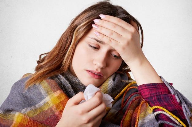 Аллергическая женщина испытывает головную боль из-за заложенного носа, держит руку на лбу, имеет высокую температуру, плохо себя чувствует. недовольная самка простужается, пытается согреться под пледом, натирает нос тканью