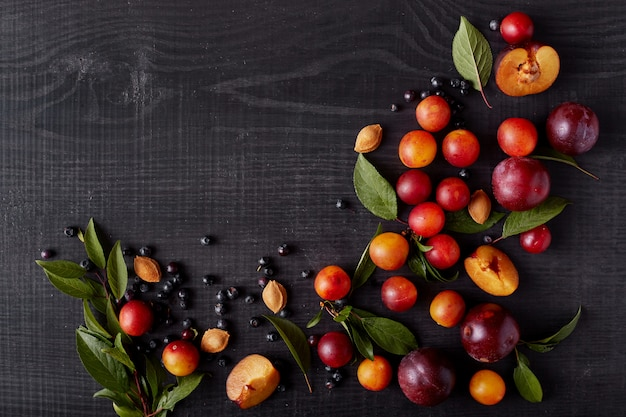 暗い木製の表面、ブルーベリー、アリッヒ、プラム黒いテーブルの上に分離されたフルーツの画像は、広告やプロモーションテキストのスペースをコピーします。健康食品、健康的な食事、ビタミンの概念。