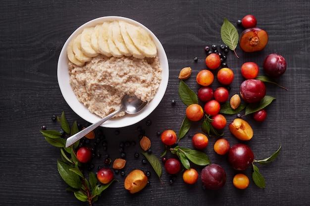 暗い木製のテーブルに白い深いボウルにバナナとオートミール。オートミールと新鮮な有機ベリー、プラム、アリケ、緑の葉で飾られたテーブルのある健康的な朝食。健康食品のコンセプトです。