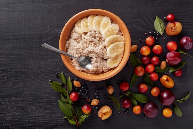 暗い木製の表面にバナナ、アリッヒ、プルーン、ブルーベリー、ピット、緑の葉とオートミールのイメージ。美味しくてヘルシーな朝食、ビタミンの入ったテーブル、フルーツのついたおやつ。健康的な食事のコンセプトです。