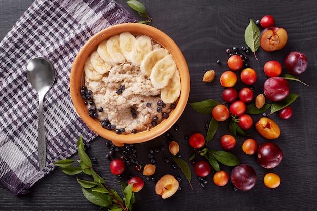 フィットネス、図、身体、健康食品のコンセプト、暗い木の表面にオートミールとバナナの白いプレート、黒いテーブルにフルーツ、プラム、アリケ、緑の葉で飾られた家族の朝食。