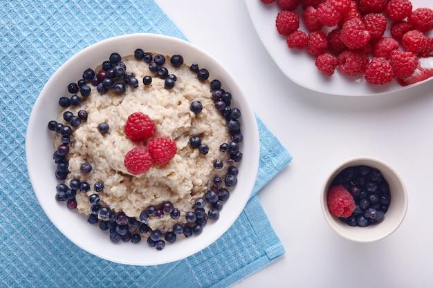 自家製のビーガンブレックファスト、白いキッチンテーブルの上のオートミールと新鮮な果物の果実とプレートの写真、机の上の青いタオルで朝食のフラットトップビュー。健康的な食事と健康管理の概念。