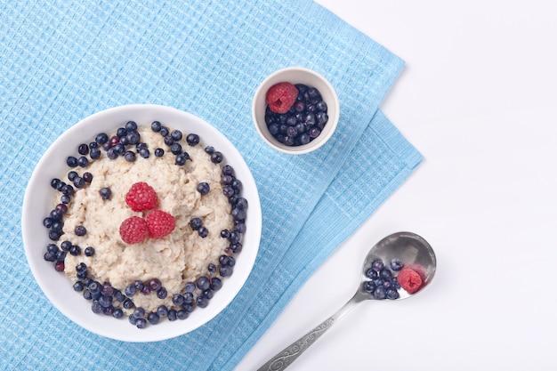 イチゴとラズベリーのオートミールのディーププレートの写真は、青い綿タオルが置かれている繊細な白い木の表面に立っています。健康的な食事、朝食、健康食品、ダイエットのコンセプトです。