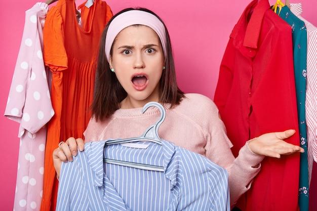 口を開けて驚いたブルネットの女性は、手のひらを発生させます。暗い髪の女の子は、青い縞模様のブラウスとハンガーを保持しています。女性はシャツがとても高いのが嫌いです。女性はショールームでセーターとヘアバンドを着ています。
