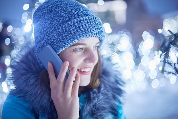 Боком портрет красивой молодой женщины носит модную зимнюю шапку и пиджак имеет телефонный разговор на открытом воздухе
