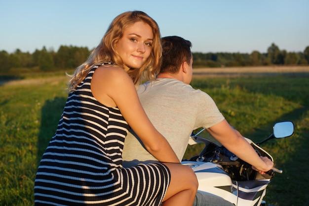 楽しいライド。バイクに乗る若いカップル。ハンサムな男とバイクのきれいな女性。旅行でそれらを楽しんでいる若いライダー