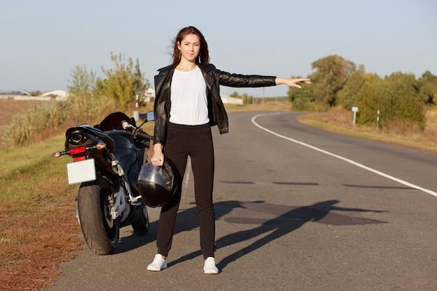 Горизонтальный снимок профессиональной женщины-байкера стоит возле мотоцикла броккен, носит кожаную куртку, держит шлем, путешествует автостопом на обочине