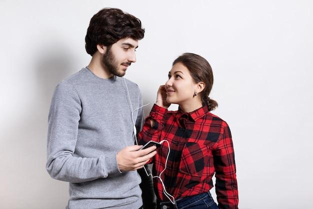 若い大人のカップルがお互いを見て一緒に音楽を聴く。スマートフォンから音楽を共有するイヤホンで幸せなカップル