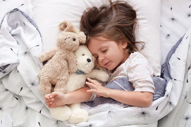 ベビーベッドでおもちゃで寝ているかわいい女の子。ベビーベッドで寝ている幼児の肖像画を間近します。熊のぬいぐるみと犬と一緒に寝ている美しい幼児