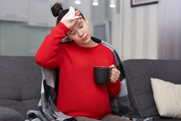 ストレスの多い女性の写真に病気の表情があり、頭痛に苦しんでいるため額に手を当てている、組織を保持している