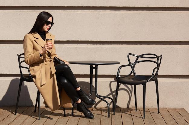 ブルネットの美しい若い女性はテラスに座って、芳香のホットコーヒーを飲み、ベージュと黒の外観