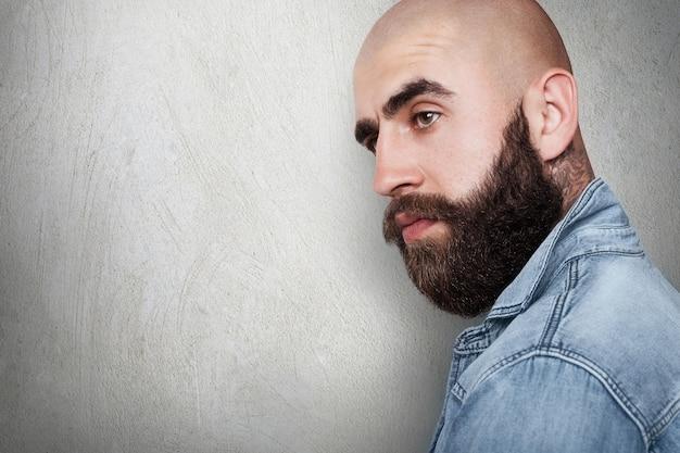 Боковой портрет с копией пространства модного лысого хипстера с татуировкой на шее, густыми черными бровями и бородой