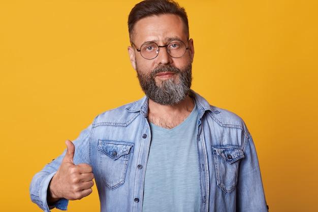 Приятный и красивый мужчина в солнечных очках, джинсовой куртке и серой футболке, поднимая большой палец вверх и