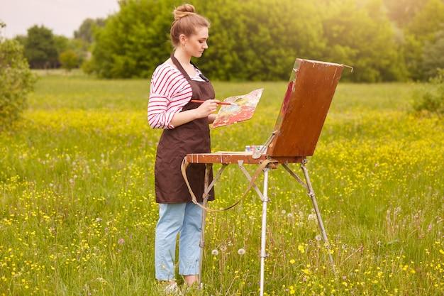 Крупным планом портрет молодого привлекательного художника на открытом воздухе, хорошо на масляной живописи. милая леди рисования пейзаж