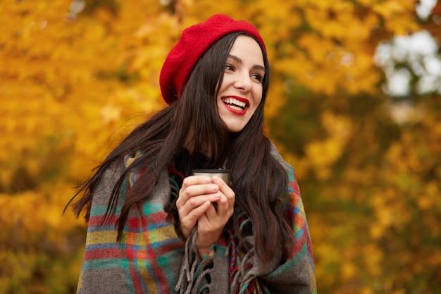 Счастливая женщина в стильном красном берете и завернутом в теплое клетчатое одеяло, смотрит в сторону и смеется, держа в руках термос