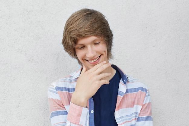 彼の頬にえくぼを持っているあごに手を握って見下ろしているカジュアルなシャツを着てトレンディな髪型で内気な少年を笑顔の肖像画