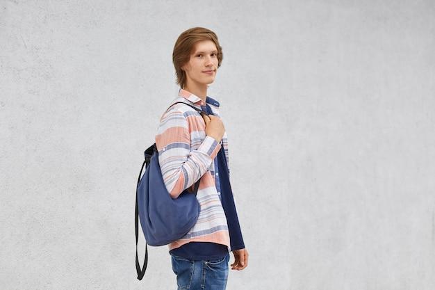 Подросток стоял боком, держа в рюкзаке рубашку и джинсы, позирует против белого бетона