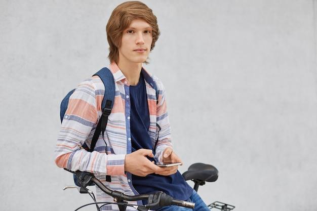 人、旅行、技術、レジャー、ライフスタイルのコンセプト。現代のスマートフォンを手で保持して彼の自転車の近くに立っている若い男性
