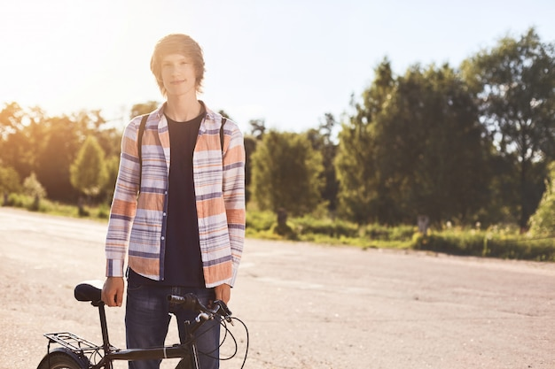 人、スポーツ、レジャー、アクティブな健康的なライフスタイル。彼の自転車の近くに立っているシャツを着ている若い流行に敏感な自転車の肖像画