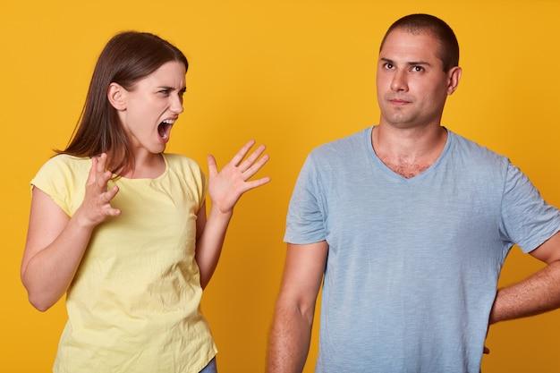 Изображение кричащей сердитой женщины, поднимающей руки, ссорившейся с мужем, смотрящей на него с гневом