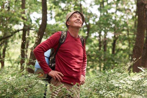 古い高齢者の旅行者の写真は森の道を散歩し、何気なく身に着けて、敷物が付いているバックパックを運び、腰に手で立っています