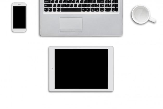 白い表面に横になっている現代のガジェット。ラップトップコンピューター、タブレット、スマートフォン、白い壁に白い空のカップ。ネットサーフィンや仕事に必要な最新のデバイスの平面図。技術