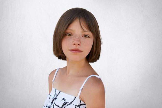 Симпатичная брюнетка с веснушками и короткими волосами позирует на белой бетонной стене в белом платье. маленький ребенок с темными широкими глазами и веснушчатой кожей, изолированными над белой стеной