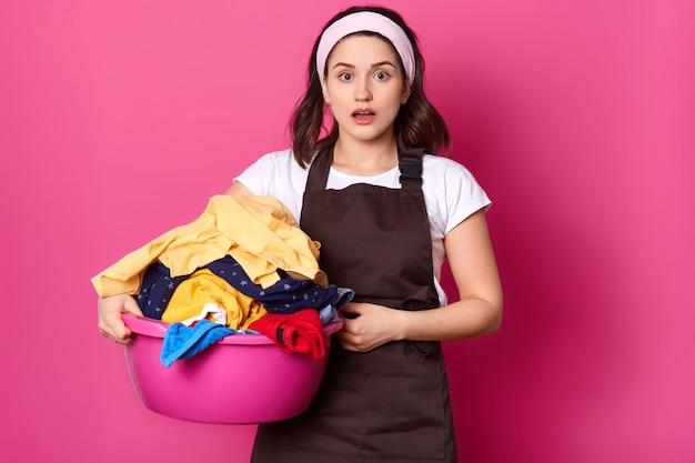 ヨーロッパの主婦は汚れた服でいっぱいの洗面器を保持し、口を開けて立って、明るいピンクの壁に孤立したポーズで表情に衝撃を与えました。世帯および家事の概念。
