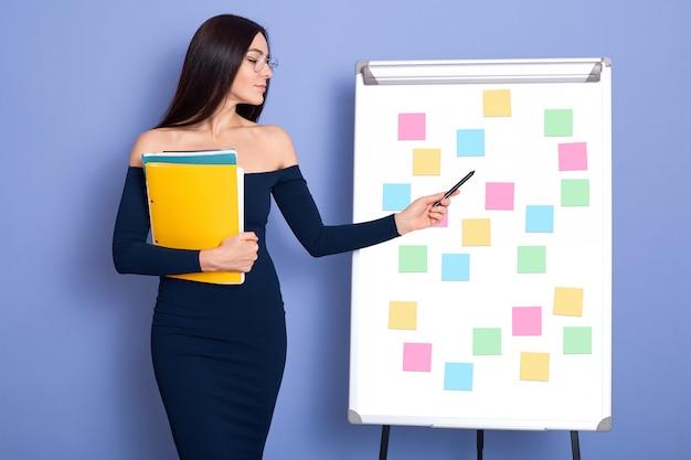 クリップボードに色とりどりのステッカーを指して、ドレスを着ている女性の手で紙のフォルダーと青い壁に分離されたポーズの若い女性の肖像画。ビジネスとライフスタイルのコンセプトです。