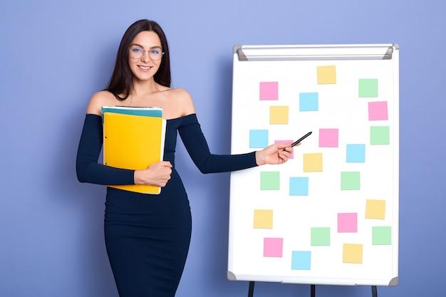 色とりどりのステッカーメモ付きホワイトボードの横にあるオフィスで魅力的な笑顔の白人女性、彼女のスキームを指している裸の肩を持つ少女、ドレスとメガネを着ている女性は、フォルダーを保持しています。