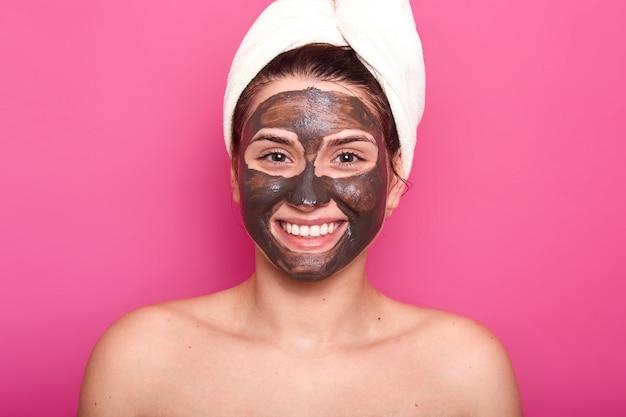 Возбужденная счастливая женщина позирует с зубастой улыбкой и шоколадной маской для лица, с обнаженными плечами, заботится о своей красоте и внешности, носит белое полотенце на голове, изолированное над розовой стеной.