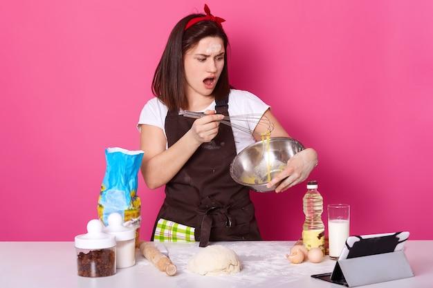 キッチンで卵を泡立てる女性のスタジオショットは、驚きの表情、自家製のペストリーを作る、ケーキを焼く、テーブルの近くに立つ、さまざまな食材に囲まれています。ベーキングおよび調理の概念。