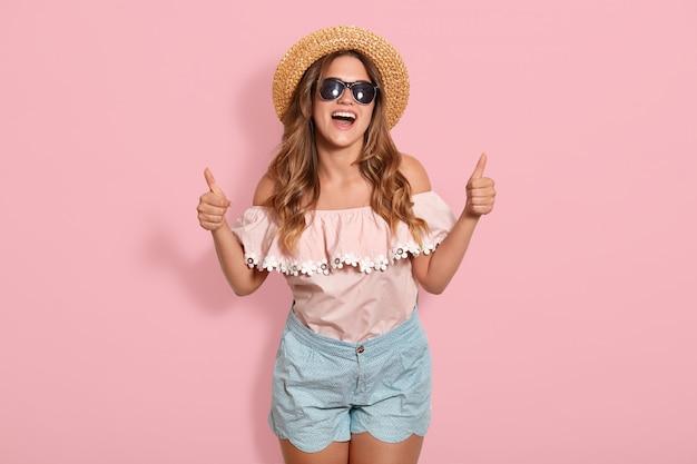 Крытый выстрел привлекательная молодая счастливая женщина с длинными волосами, носить стильную одежду, позирует с вдохновенным выражением лица. активная молодая женщина в соломенной шляпе, с удовольствием в помещении, указывает большой палец вверх.