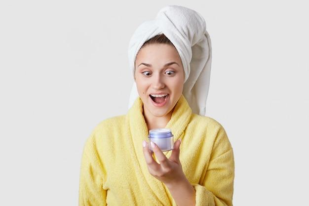 うれしそうな驚いた女性は高価なフェイスクリームを見て、顔に塗るつもりです。白いバスタオルと白いタオル、白い壁にモデル。人、美容治療、衛生概念。