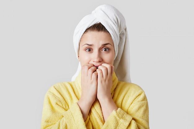神経質な心配の女性は指の爪を噛み、ボーイフレンドとのデートの準備をし、何を着るか、どのようにメイクアップするのかわからない、白い壁に隔離された家庭用の服を着ています。ウェルネス。