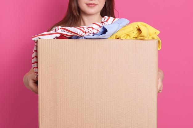 段ボール箱を手に立って、バラ色の壁に分離されたファッショナブルな服のカートンボックスを保持している顔の見えない少女の屋内ポートレート。寄付、チャリティー、ボランティアのコンセプト。