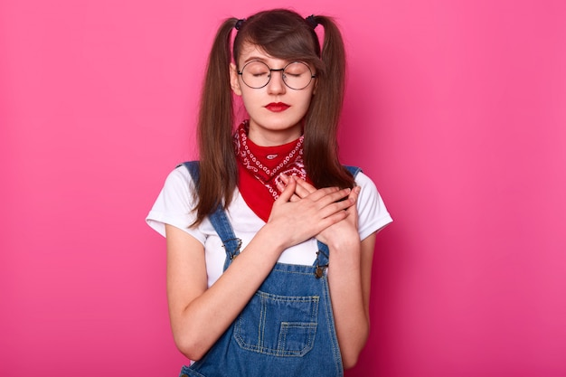 目を閉じた細身の魅力的な女の子は、胸に両手をまっすぐに横切って立ち、心拍を感じようとし、穏やかで穏やかに見えます。若者、スタイル、感情。広告用のスペースをコピーします。