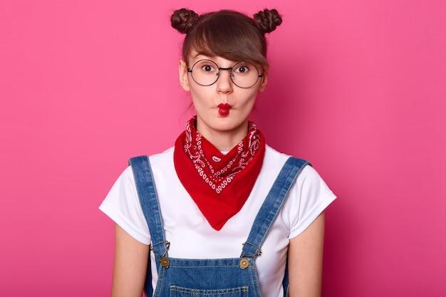 Крупным планом крытый портрет смешная красивая молодая брюнетка девушка, очаровательный подросток дурачиться, делать гримасу, имеет смешные выражения лица, глядя прямо на камеру, изолированную над розовой стеной.