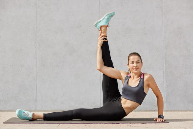 Красивая спортивная молодая женщина в стильной спортивной одежде, работающей в помещении против серой стены, женские сидят на полу, делая упражнения на растяжку после тяжелых тренировок, держит себя в форме.