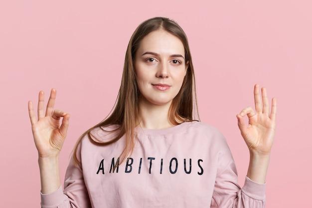 Очаровательны молодая европейская женщина с длинными темными волосами показывает хорошо знаком, жесты руками, одетые случайно, выражает свое согласие, изолированных на розовой стене. утверждение и концепция языка тела