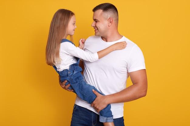 ハンサムな父親が小さな娘を運ぶ水平方向のショット、黄色の壁に孤立したポーズのモデル、パパと彼の子供がお互いを見て、カジュアルな服を着ています。家族の概念。