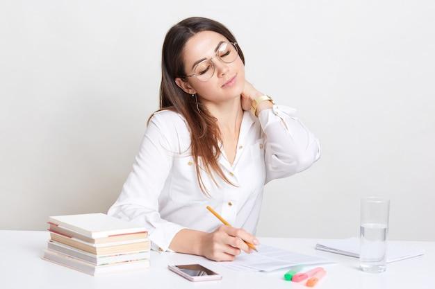 忙しい女性の画像は首に手をつないだり、ドキュメントでの長い仕事の後に疲れたり、職場に座ったり、出版物を作成するための創造的なアイデアを書いたり、目を閉じたり、携帯電話で電話を待ったりします