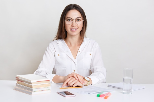満足している女性建築家はデザインを学び、コースの準備に時間を費やし、科学文献を使用し、文書に記入し、白い壁に分離された丸い眼鏡をかけています。