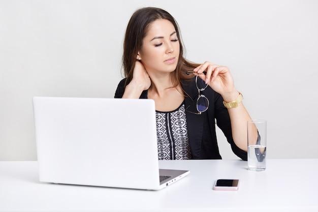 疲れている白人女性の画像は、ポータブルラップトップコンピューターで長時間働いて、眼鏡を手に持ち、首に痛みを感じ、現代のテクノロジーに囲まれ、白い机に座って、屋内でポーズをとっています