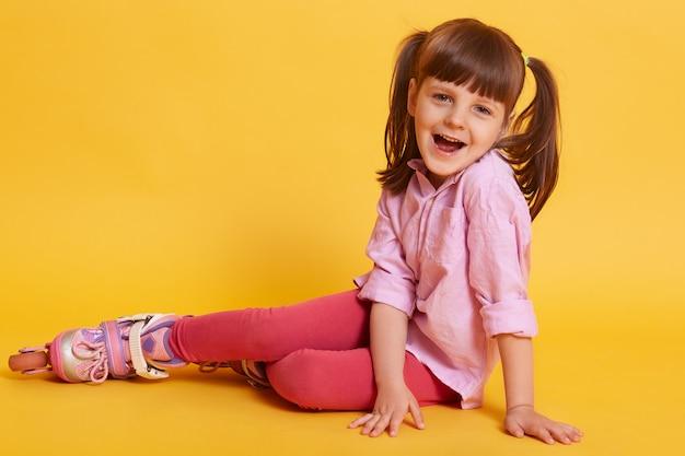 Горизонтальное изображение маленькой девочки, широко открывающей рот, находящейся на полу, носящей роликовые коньки, находящейся в хорошем настроении, весело проводящей время. концепция детей и досуга.