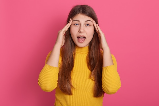 Портрет потрясенной эмоциональной молодой леди, широко открывающей рот и глаза, кладущей руки на виски, с головной болью, стрессом, болью, проблемами со здоровьем люди и стресс концепции.