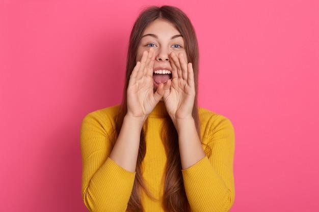 Портрет энергичного громкого милого красивого женского открытия рта широко, помещая руки в рот, крича, делая шум, стоя изолированный по розовой стене в студии, нося повседневную одежду.